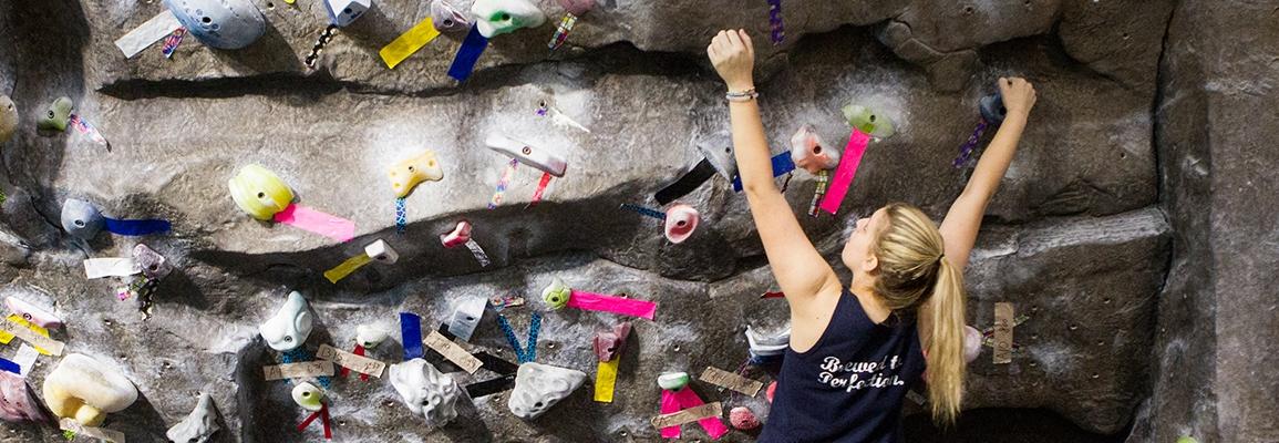 Student bouldering at Appalachian SRC's climbing wall